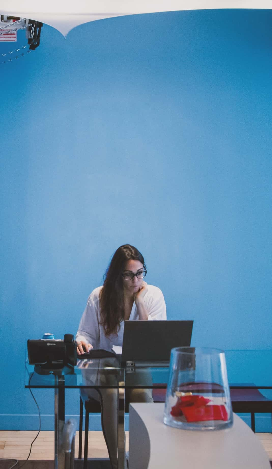 Tall photo of a woman working on her computer at a desk. Contact Us for more information about our services