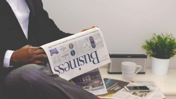 Man sitting, reading the business section of the newspaper